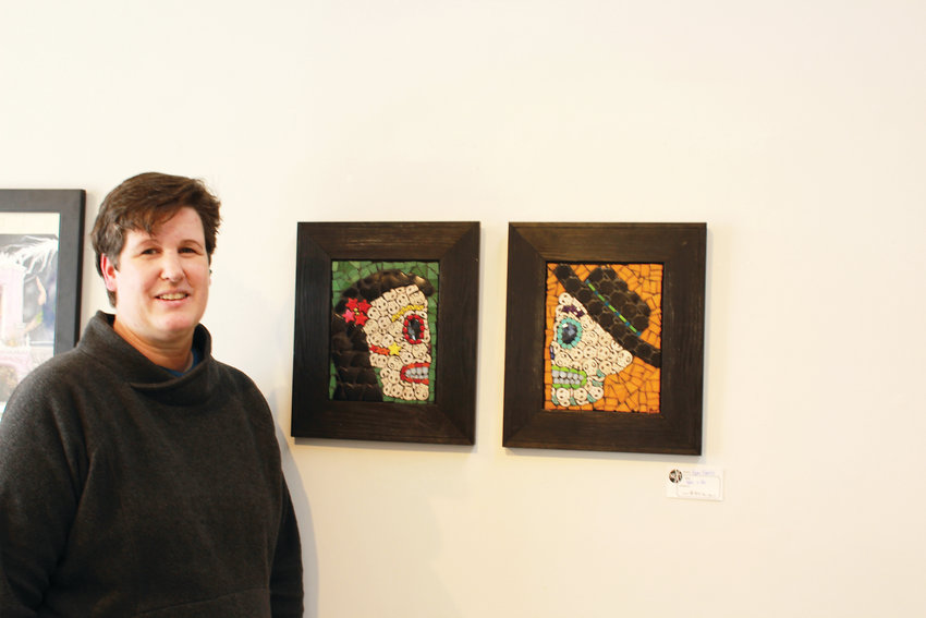 Pam Farris poses next to two of her paintings.