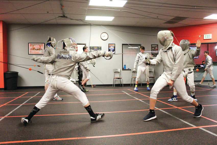 Two fencers spar during practice at the Fencing Academy in Parker.