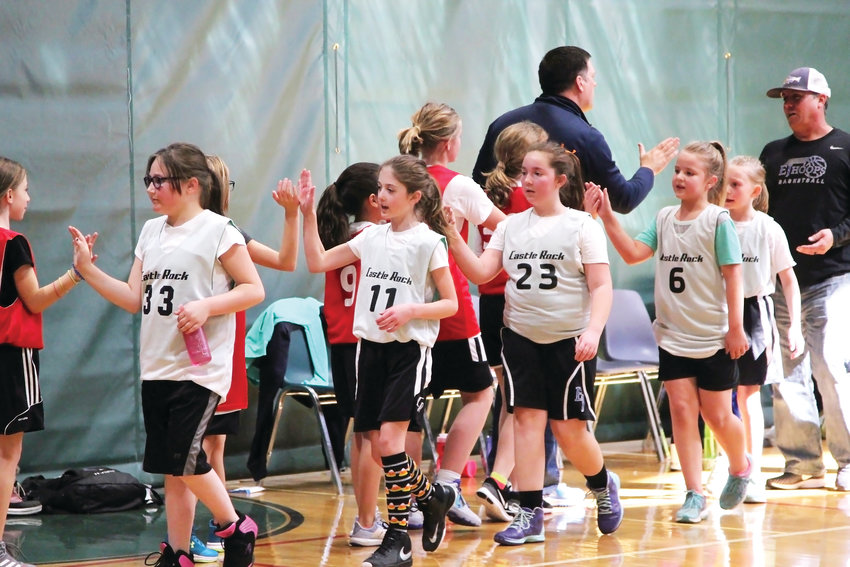 Players form the 4th-grade age bracket give each other high-fives at the end of their basketball game on Feb. 23.