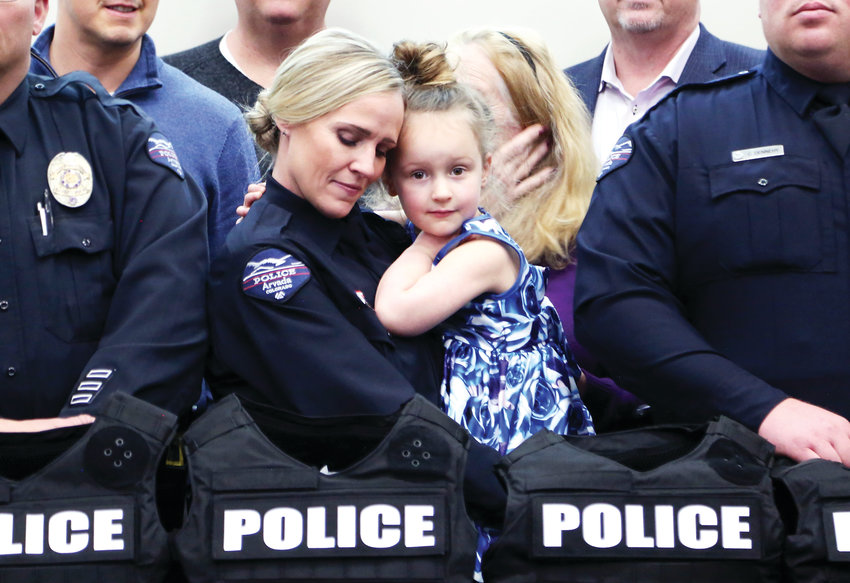 Arvada Police Officer Melinda Rommereim holds her four-year-old daughter, Paisley, after receiving her armor kit from SHIELD 616.