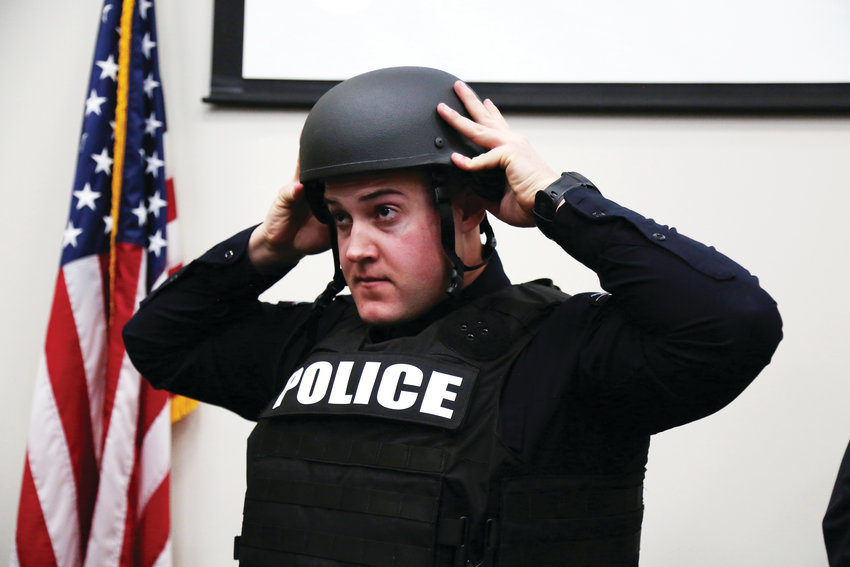 Arvada Police Officer Robert LoBosco tries on his new ballistic helmet and armor vest donated by SHIELD 616.