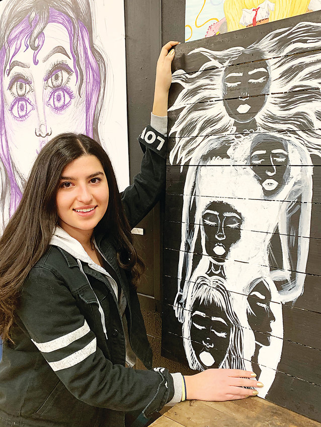 Darryah M. AlSaaid, Littleton High art student with her painting showing many faces-turned in various directions. She is focused on identity and what makes up a person.