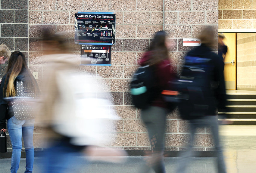 Students at Lakewood High School walk past vaping education posters in the hallway. The Colorado Department of Public Health and Environment says Colorado is first in the nation for the number of teenagers who use vaporizers or e-cigarettes, calling the trend a public health crisis.