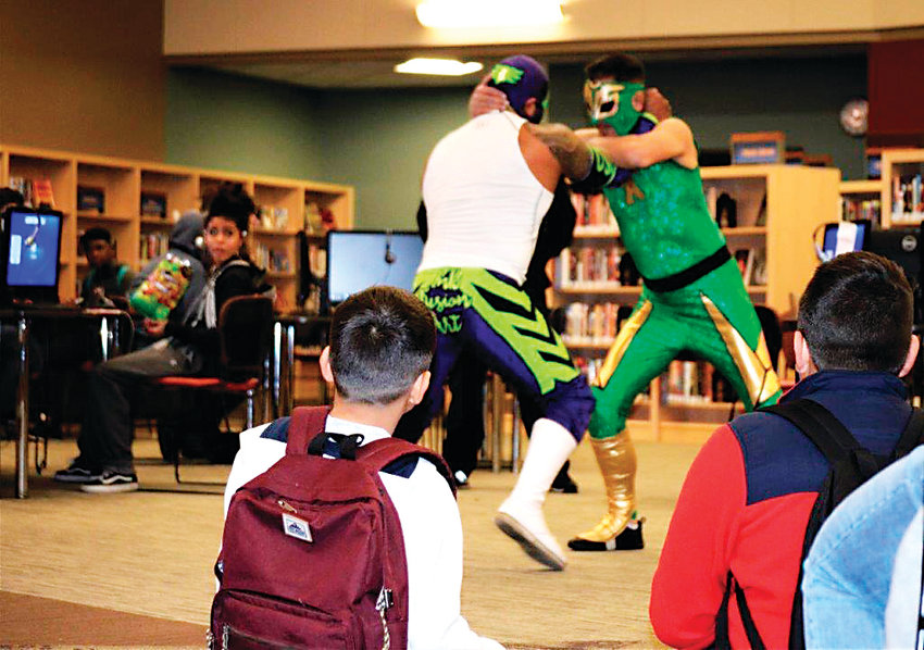 Professional wrestlers, or luchadores, Heros, in white, and Sol Azteca, square off in the middle of Anythink Library's York St. branch Feb. 26. Anythink Guide Michelle Hawkins invited the pair to the library to show off some of their moves and talk to the patrons about what Mexican wrestling means to them.