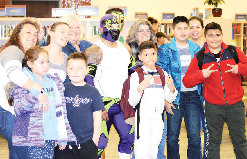 Mexican wrestlers Heros, in white, and Sol Azteca in green pose with Anythink Library patrons and staff Feb. 26 after presenting a demonstration of their craft and talking about it.
