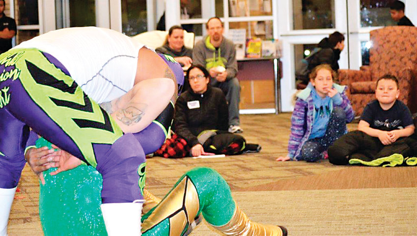 Anythink Library York St. patrons watch as luchadores Heros and Sol Azteca trade moves Feb. 26.