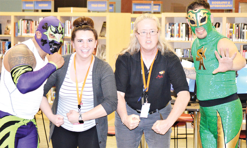 Anythink Library York Street concierges Gina Collette, left, and Heather McCuistion pose with luchadores Heros and Sol Azteca Feb. 26. The pair of Mexican wrestlers both work in Denver through Lucha Libre Life and showed off their moves at the library.