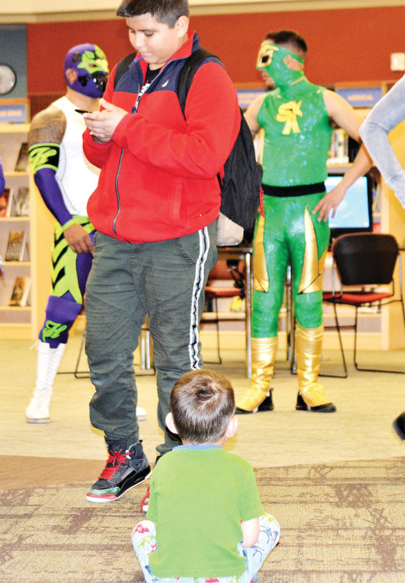 Four-year-old Jesus Martinez sits and refuses to move as library patrons go up to meet luchadores Heros and Sol Azteca Feb. 26 at the Anythink Library York Street branch.