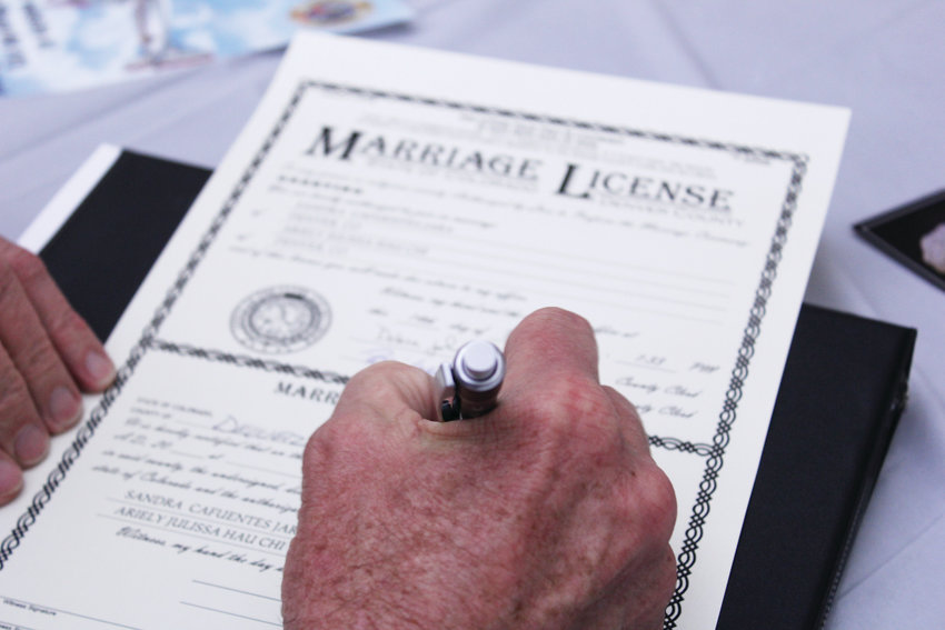 An officiant fills out a wedding certificate for a couple married in Denver on Valentine's Day. The city has offered wedding ceremonies on the holiday for the last 12 years.