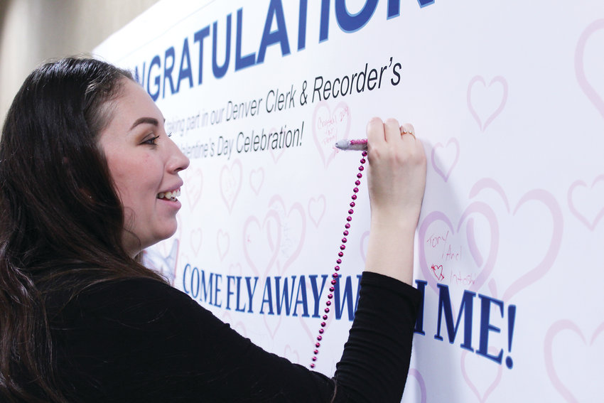 Lorena Sigala signs a poster in the Webb Municipal Building after getting married on Valentine's Day. She said she felt blessed to have her family there to celebrate with her.