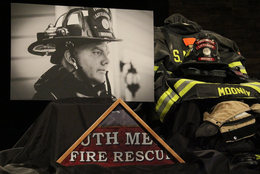 A photo of Cody Mooney and his firefighting helmet and gear sit on the stage at Mission Hills Church in Littleton March 8, where a memorial service was held for Mooney.