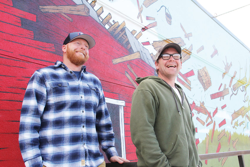 Jason Sakry, left, and Dagan Thomas stand March 7 in front of the mural on the side of Barnhouse Tap, a bar at 4361 S. Broadway in Englewood. The bar, which opened in December, hopes to establish itself as a go-to place for the surrounding neighborhood.