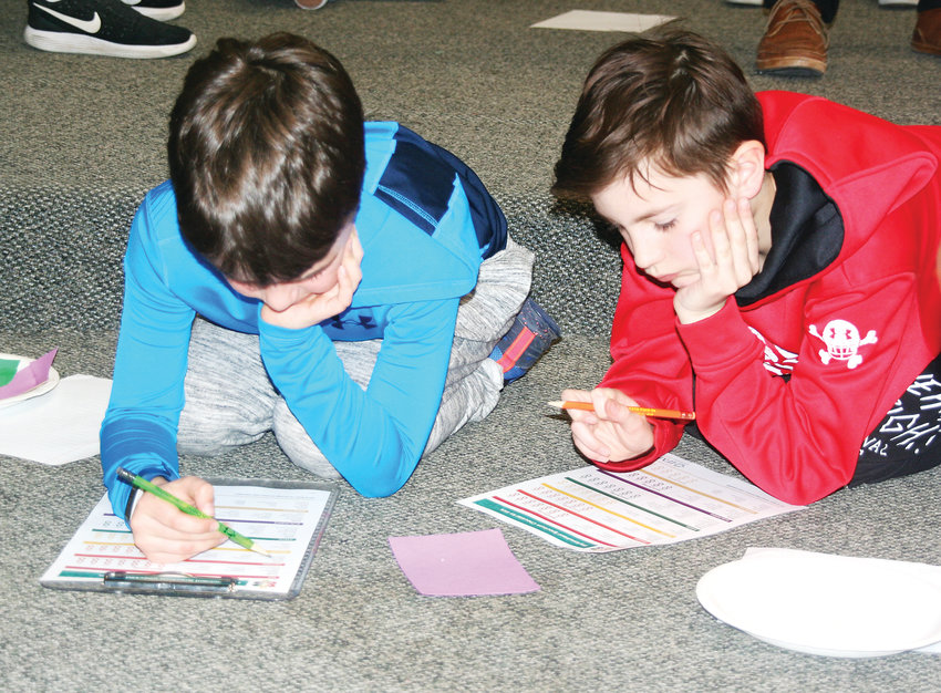 Ben Smith, left, and Luca Snowhawk, both fourth-graders at Compass Montessori-Golden Campus, work together on a worksheet that allowed the students to plan out meals that contain phytonutrients during the March 5 FOOD MATTERS workshop.