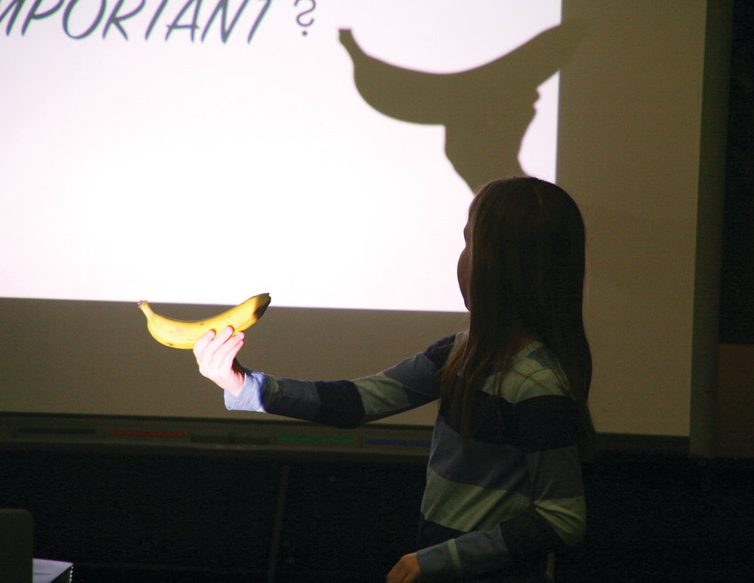 Cora Studeny, a fourth-grader at Compass Montessori-Golden Campus, holds up a banana during the FOOD MATTERS workshop for the fourth-through-sixth-grade students on March 5.