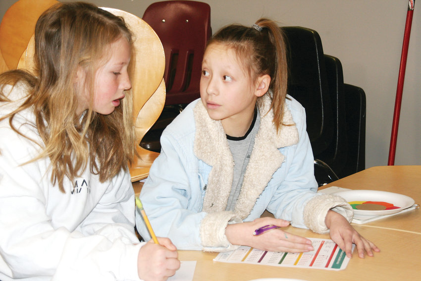 Fifth-grader Maizy Freestone, left, and sixth-grader Sienn Garcia engage in conversation about phytonutrients during a FOOD MATTERS workshop on March 5 at Compass Montessori-Golden Campus.