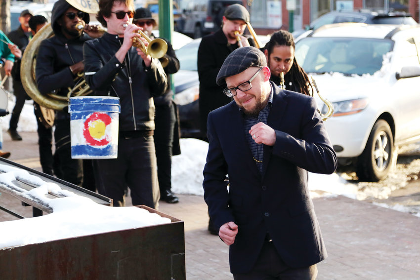 Joseph Hengstler, executive director of the Arvada Business Improvement District, leads the brass band into Denver Beer Co. to end the Fat Tuesday parade.