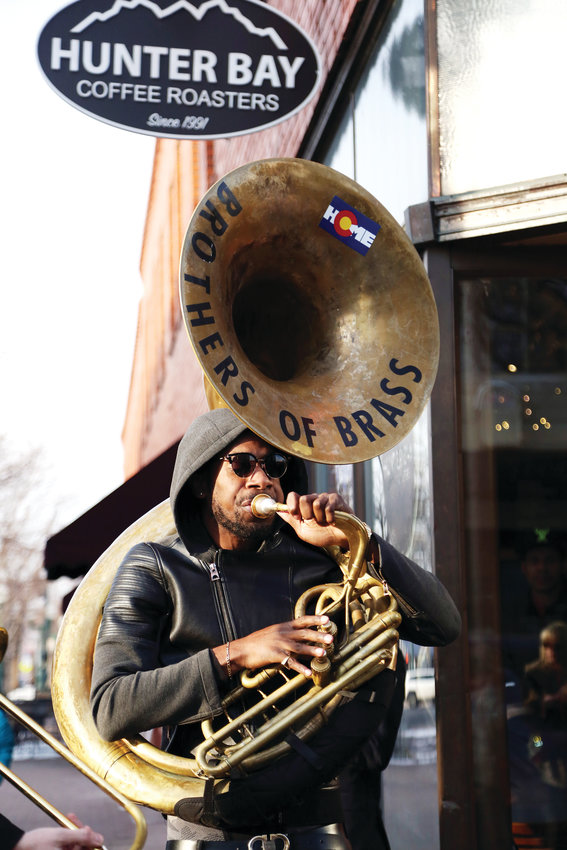 Khalil Simon plays tuba with the Brothers of Brass band while walking the streets of Olde Town Arvada.