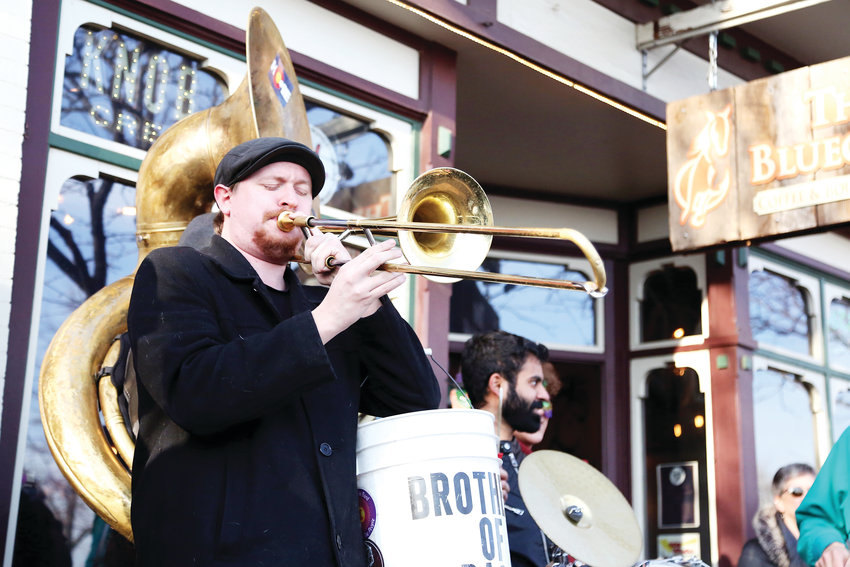 Ethan Harris plays trombone with Brothers of Brass during the Fat Tuesday kickoff parade in Olde Town Arvada.
