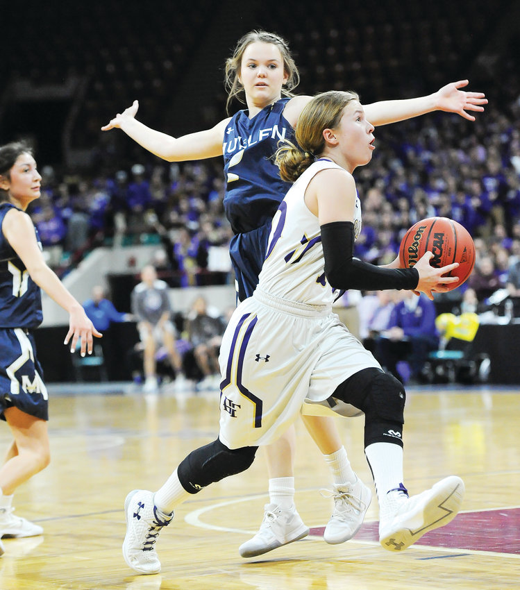 Holy Family senior point guard Kaitlyn McKenzie drives around Mullen's Colleen Hart, during 2nd quarter action of the March 7 CHSAA Girls 4A semifinal game at the Denver Coliseum. The Mustangs easily defeated the Tigers, 55-33, ending Holy Family's state championship run.