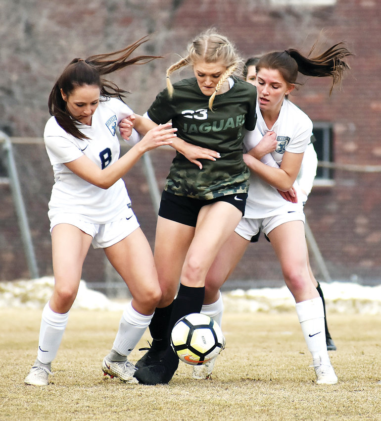 D'Evelyn senior Laryssa Hamblen (23) fights through Columbine seniors Libby Spangler (8) and Melaini Jamison during the season opener for the Jaguars and Rebels on Friday, March 8, at Lakewood Memorial Field.