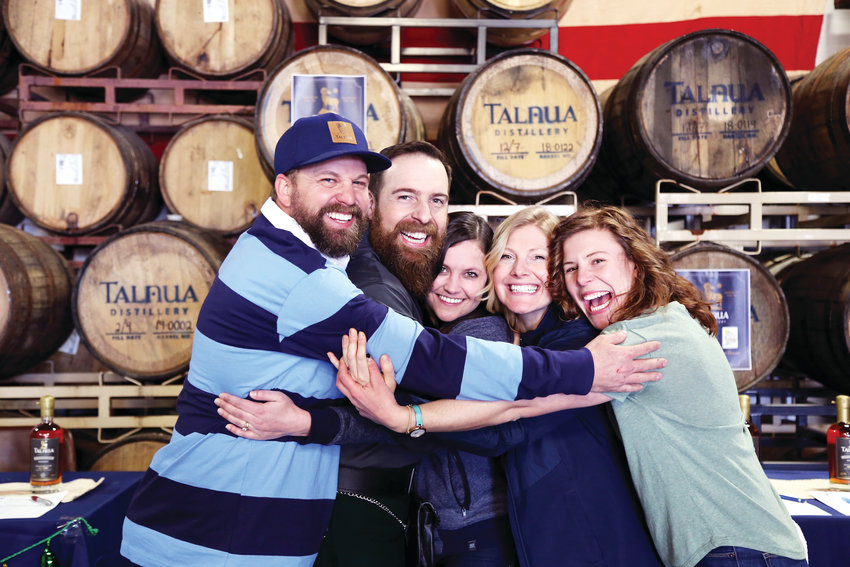 Robert Siegrist, Patrick Miller, Meagan Miller, Amy Kingman and Maya Oren group hug at the grand opening of Talnua Distillery in Arvada.