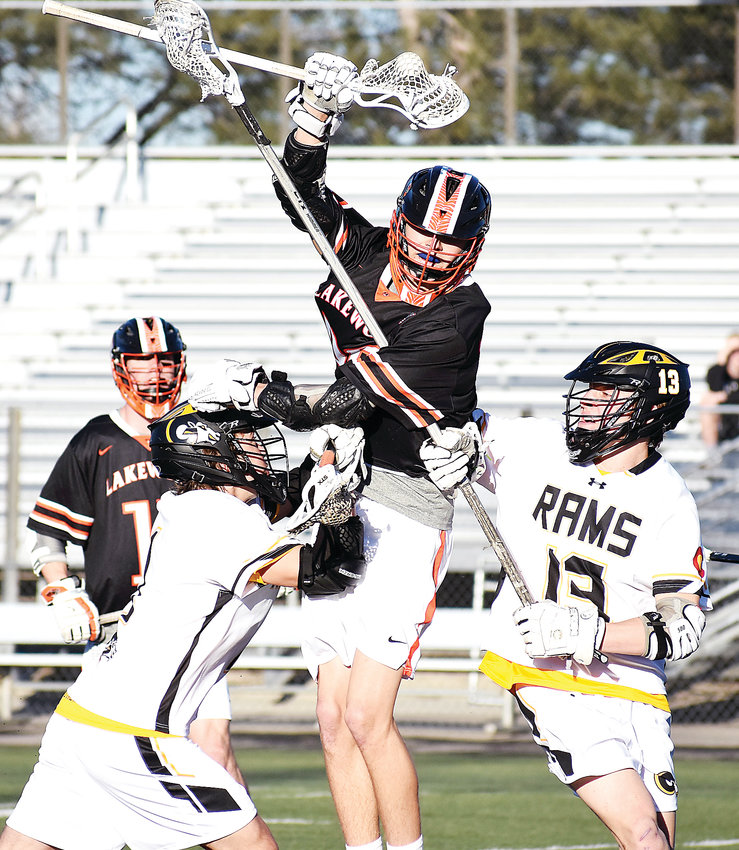 Lakewood senior Evan Woods, middle, does his best to split Green Mountain sophomore Tyler McNeilly, left, and junior Trey Corkin (13) during the first half March 20 at Trailblazer Stadium in Lakewood. The Tigers took a 13-5 victory.