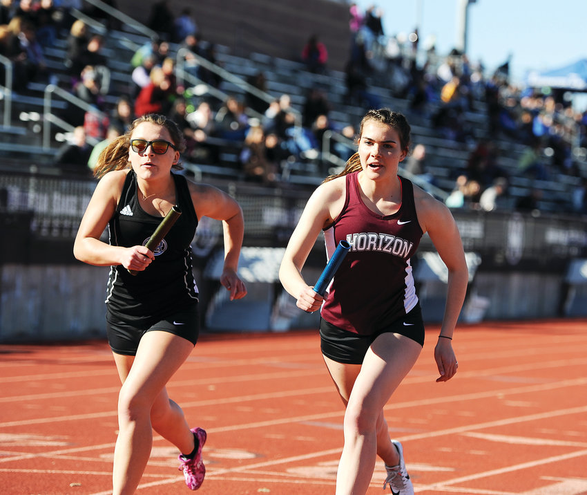Mountain Range's Jessica Croissant, left, and Horizon's Kyra Herronen run together from the starting line during a girls 4-by-800-yard relay event at the Adams 12 Five Star Invitational March 20 at District 12 North Stadium.