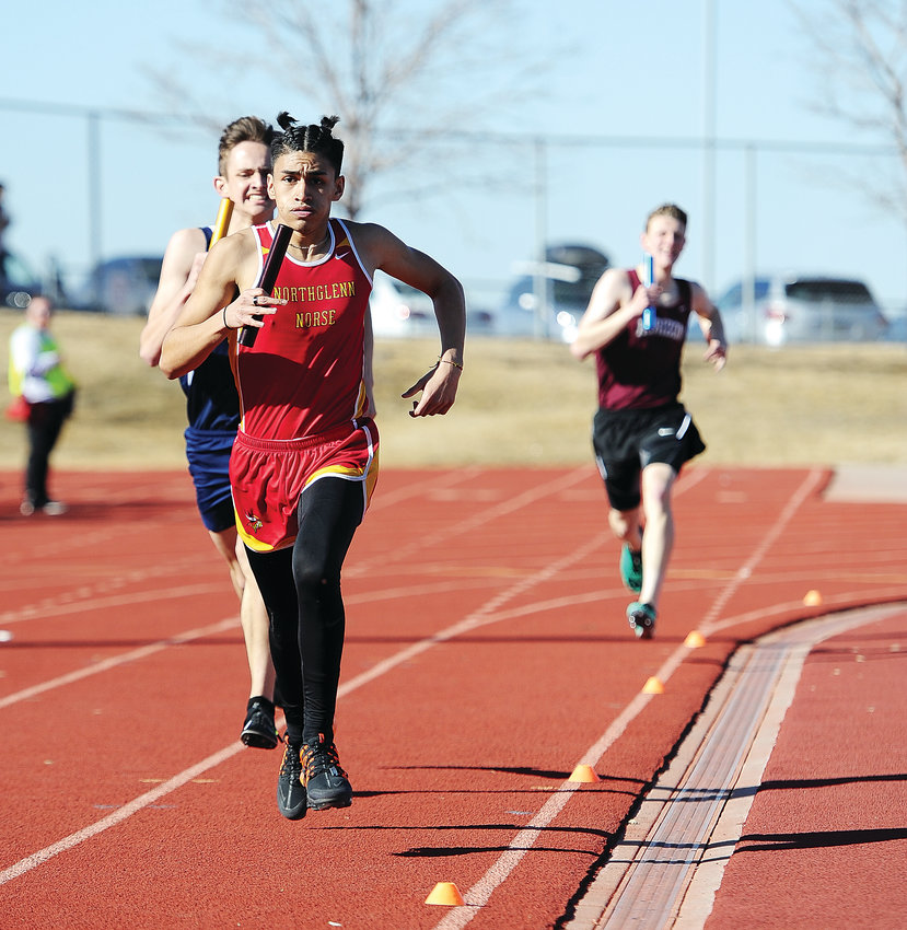 9196-Northglenn senior Julio Ramos runs ahead of Legacy's Jacob Hansard, left, during a boys 4-by-800 relay event at the Adams 12 Five Star Invitational  March 20 at District 12 North Stadium.