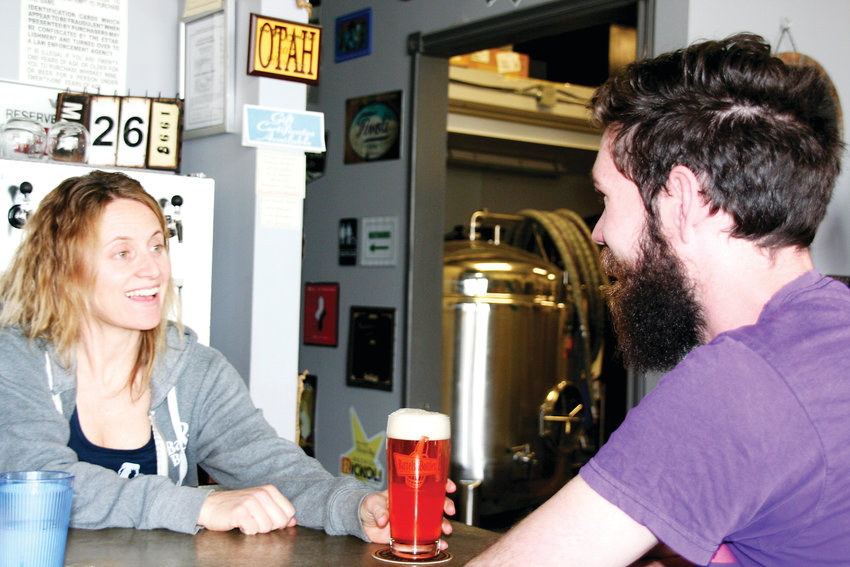 Abby George, co-owner of Barrels & Bottles Brewery, serves a beer to Gabe Bristow of Golden on March 26. Following the opening of the brewery's second location in Pleasant View, staff and ownership will still operate with the mentality of a neighborhood brewery.