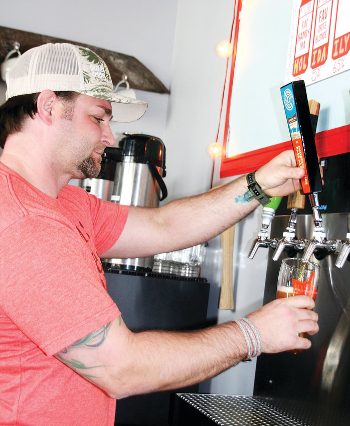 Zach George, co-owner of Barrels & Bottles Brewery, pours a beer on March 26. The brewery will soon be opening another location in Pleasant View, where most of the brewing operations will take place.