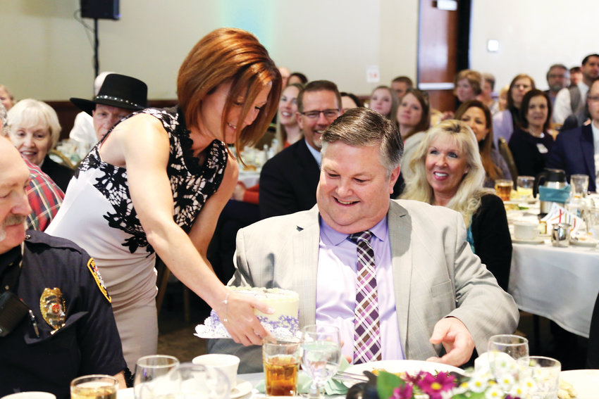 Dot Miller presents Arvada Chamber Man of the Year Jerry Marks with a birthday cake during the awards luncheon.