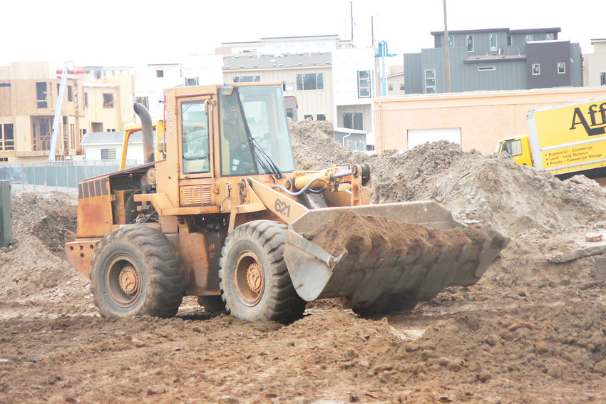 A front-end loader moves dirt behind The Belleview Connection, the strip mall formerly called Centennial Square Shopping Center. The center at Belleview Avenue and Prince Street is getting a large new building this year.