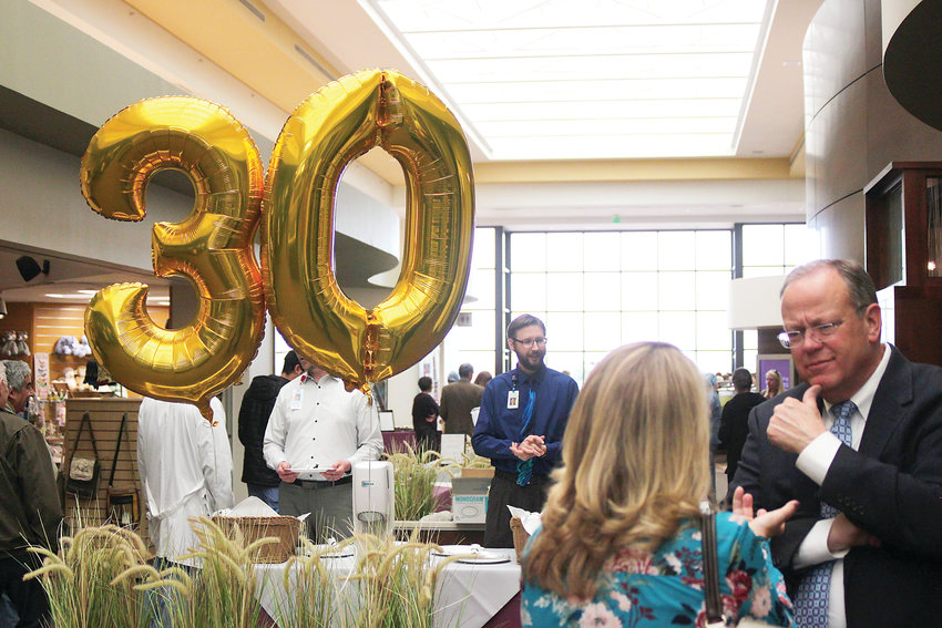 Littleton Deputy City Manager Randy Young, right, speaks to a friend in the atrium of Littleton Adventist Hospital during the center's 30th anniversary celebration.