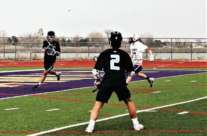 Mountain Range senior Travis Hitt makes the pass to junior teammate Jake Doyle April 2 against Holy Family.