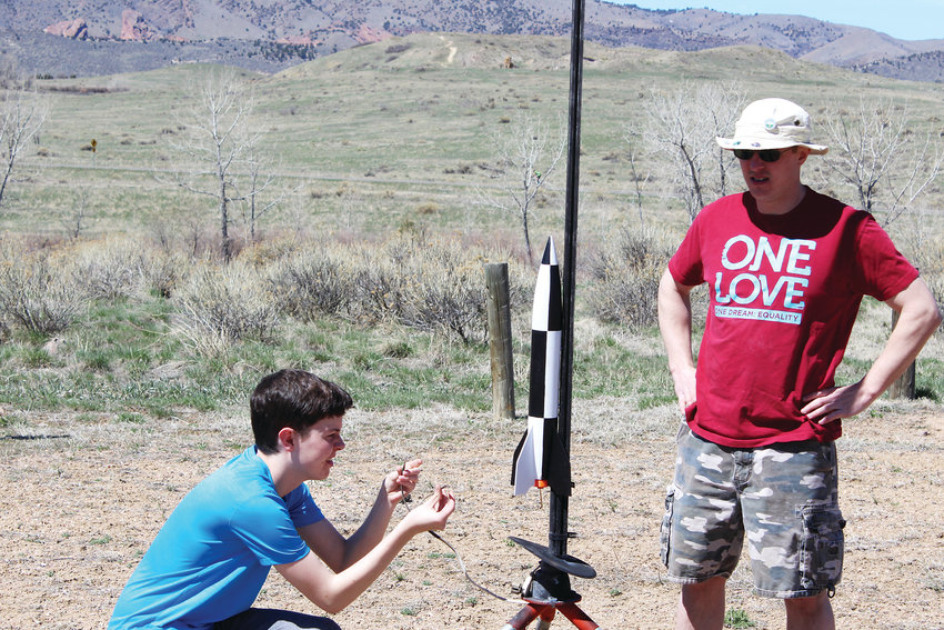 Cullen Hirstius and Joe Bowen prepare a rocket for a launch.