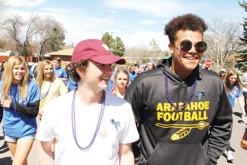 "Tyler Adams, left, and Jason Washington, seniors on the Arapahoe High School football team, talk to friends during the suicide-prevention walk April 14 in the neighborhood near Arapahoe High. ""All the guys from football that I know are here,"" Adams said."