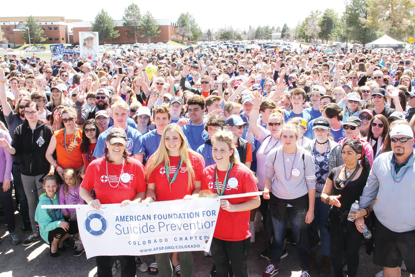 Several hundred stand behind the organizers of the Out of the Darkness suicide-prevention walk April 14 on the Arapahoe High School campus. In front, left to right, stand Melissa Hughes, a volunteer with the American Foundation for Suicide Prevention, and Brooke Smiley and Ry Renshaw, Arapahoe students.