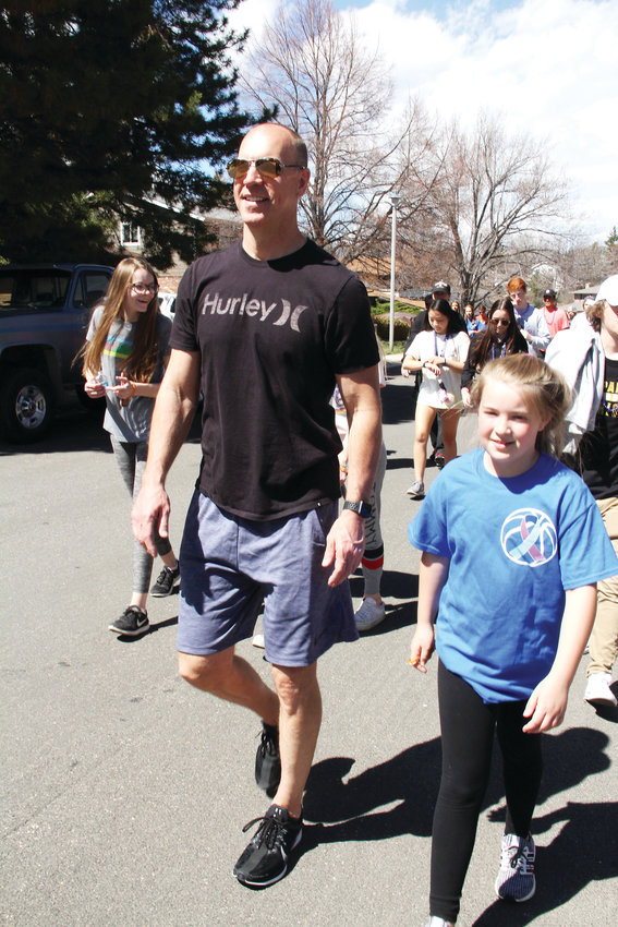 Jim Hansen, 50, and Samantha Stearns, 10, keep a brisk pace April 14 during a suicide-prevention walk in the neighborhood near Arapahoe High School. Many parents from the community like Hansen, who lives in Centennial, participated in the walk.