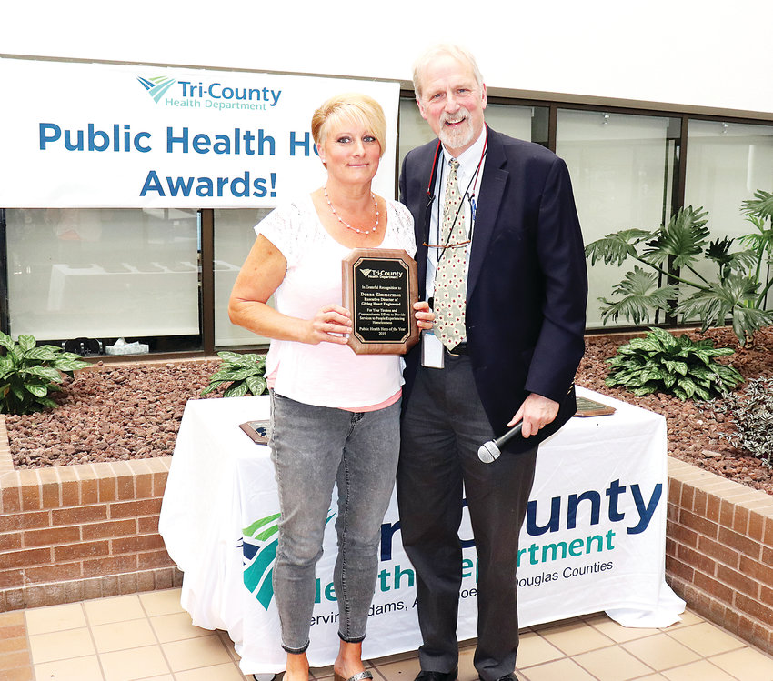 Donna Zimmerman, executive director of Giving Heart Englewood, which works with people experiencing homelessness, receives a 2019 Public Health Hero award from John Douglas, executive director of Tri-County Health Department, which serves Adams, Arapahoe and Douglas counties.