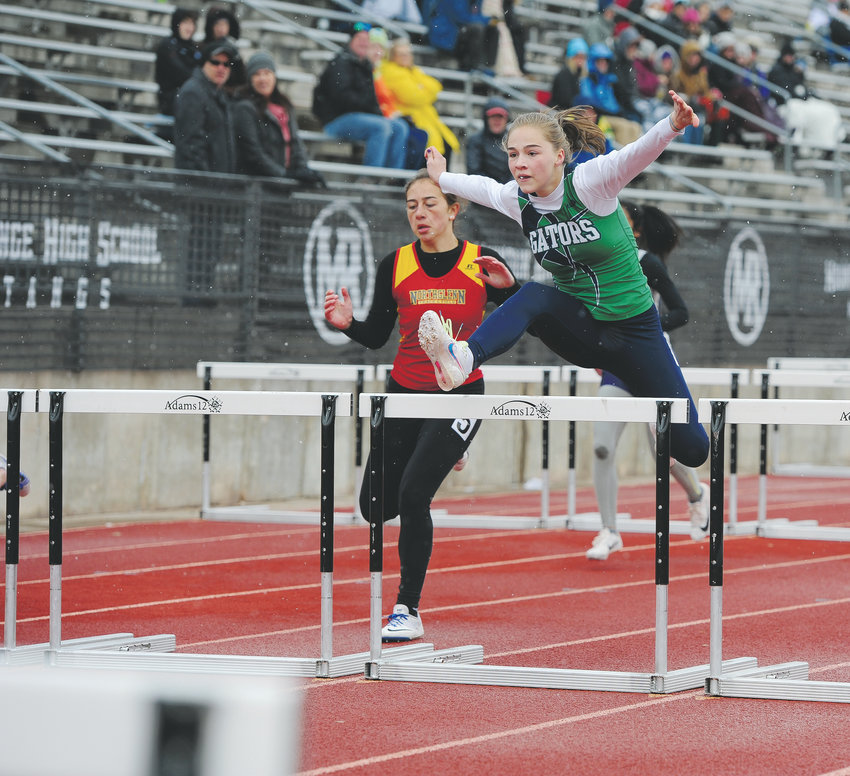 Standley Lake's Isabella Settje, right, clears a hurdle ahead of Northglenn's Melina Townsend, during a Girls 100 meter event, at the Mountain Range Invite Track and Field Meet April 13 at District 12 North Stadium in Westminster. Athletes from numerous schools competed, despite 35 degree weather and snow flurries.