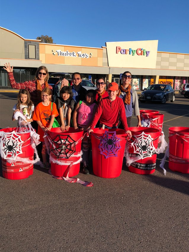 Residents participate in a trick-or-treat event at the University Hills Plaza shopping center off Colorado Boulevard. Owners and staff at the shopping center began partnering with the merchant's association there to create community events as well as a summer Farmer's Market.