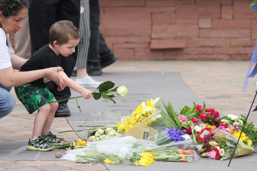 Across the park from the ceremony, a young boy lays a rose atop others at the Columbine Memorial on April 20.