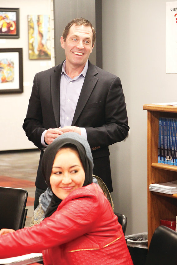 U.S. Rep. Jason Crow stands behind Afghan immigrant Adila Elhem in a citizenship class at the Littleton Immigrant Resource Center on April 15. Crow visited during a challenging time for the center, which lost a federal grant last year and is fighting fears among legal immigrants about pursuing citizenship.