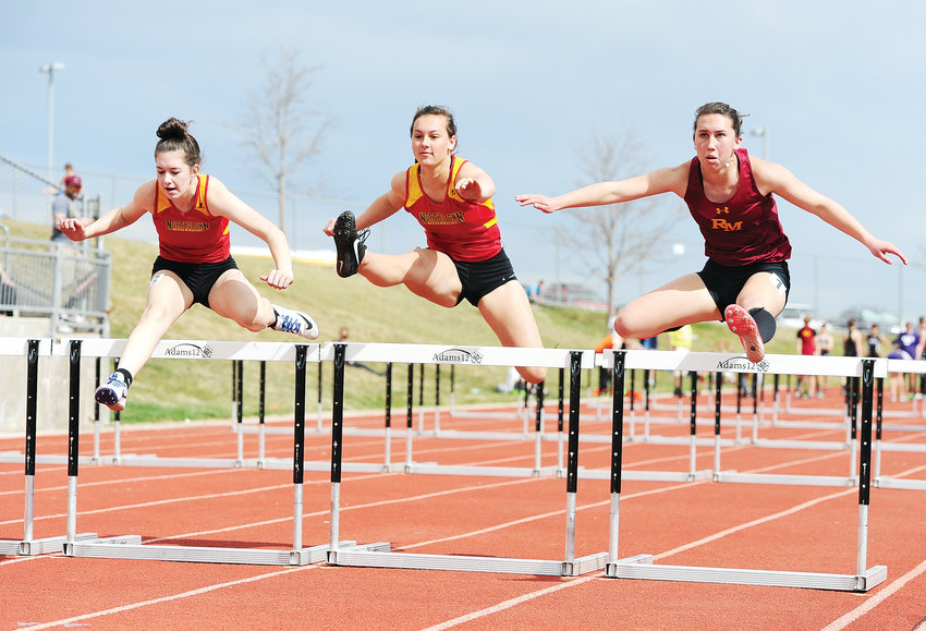 A trio of hurdlers, including Morgan Mitchell, left, and Tyler McFall, of Northglenn High School, and Rylie Durant, of Rocky Mountain High School, compete in a girls' 100-meter event