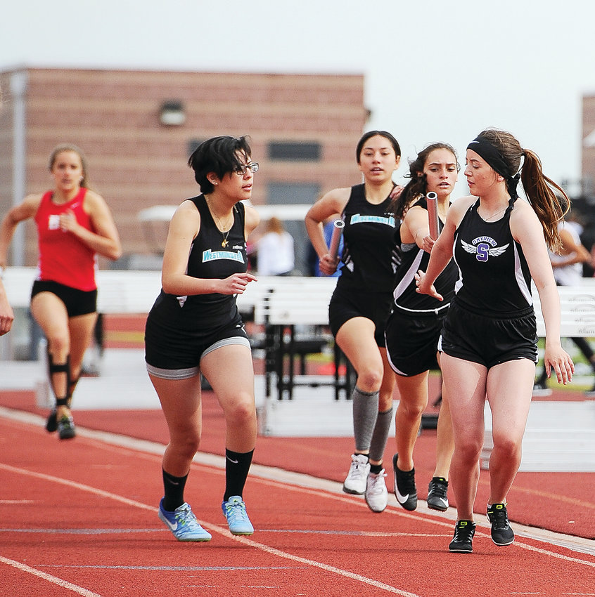 Skyview's Haley Cookson, right, prepares to receive the baton from teammate Jordan Gonzales, as Westminster High's Vanessa Portillo, left, is about to do the same, from Jackie Rodriguez, in a girls' 4 x 800-meter relay. , at the Maxine Ehrmann Thornton Invite April 20 at District 12 North Stadium in Westminster.