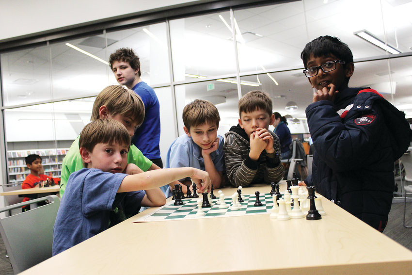A group of boys study a board, collaborating on the best moves to make. The boys are part of the Parker Chess Club, which meets every Thursday at the Parker Douglas County Library.
