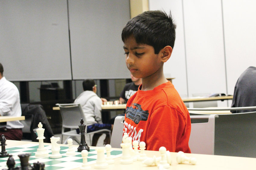 Darshan Satishkumar, 8, waits to make his next move at the Parker Chess Club. Satishkumar took third place in K-3 Colorado State Scholastic Championship, his first rated tournament. He began playing chess at 5.