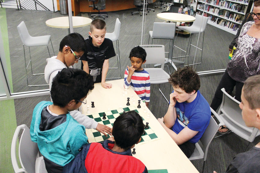 Cameron Miner, 15, faces off against a group of boys at the Parker Chess Club April 18 at the Parker Douglas County Library. The boys will team up against Miner just to defeat him before the night is through.