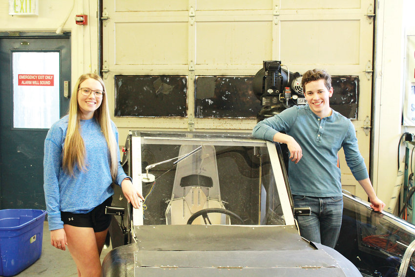 Ali Helton and Caleb Coyne pose in front of one of Wheat Ridge High School's student built hydrogen cell fuel cell vehicle.