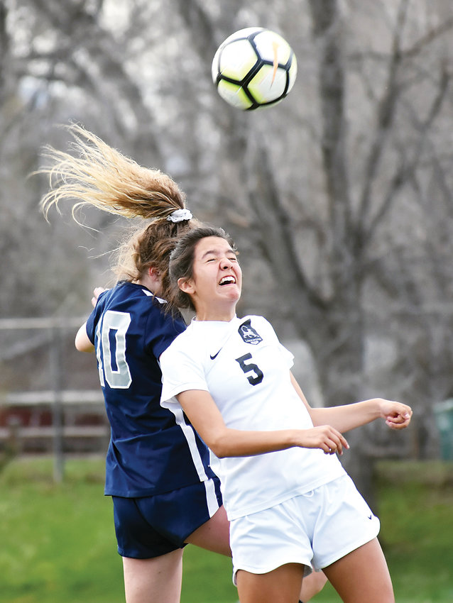 Lakewood freshman Esperanza Zarate (5) heads the ball in front of Columbine junior Tegan Marshall (10) during a conference match Monday, April 15, at Lakewood Memorial Field.